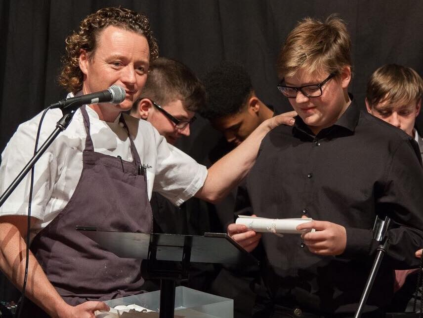 Max receiving an award from Tom Kitchin