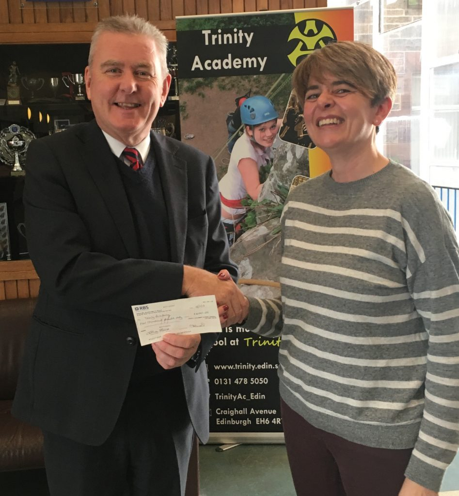 Parent Council chair Liz presenting a check to headmaster Bryan Paterson